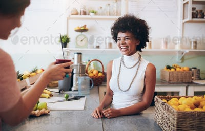 Smiling young woman talking to a customer in juice bar