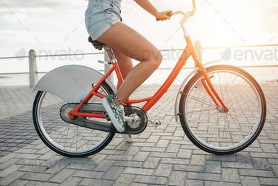 Young woman on her bike at the seaside road