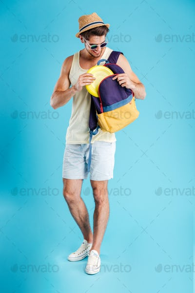 Happy young man standing and taking frisbee disk from backpack