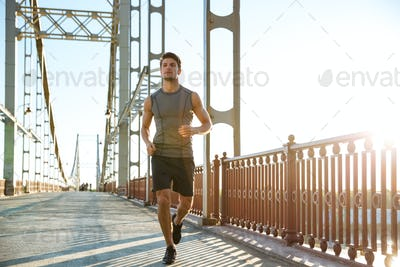 Attractive fit man running along bridge at sunset light