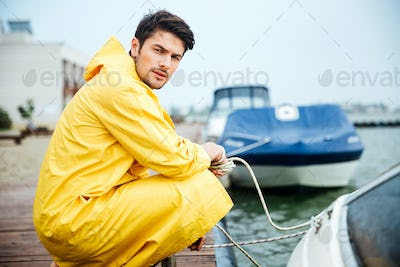 Handsome young man wearing yellow clock at the pier