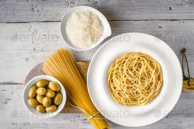 Raw and cooked spaghetti with olives and cheese
