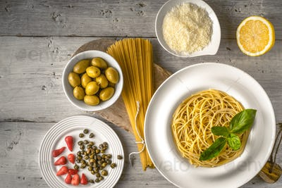 Raw and cooked spaghetti with different appetizer