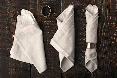 Set of the napkins with vintage ring on the wooden table top view