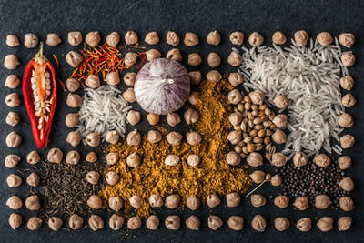 Composition of  chick-pea , vegetables and spice on the dark stone background