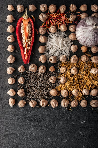 Composition of chick-pea  , vegetables and spice on the dark stone vertical