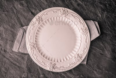 Romantic ceramic plate on the dark stone table top view