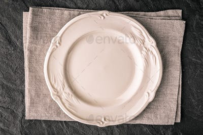 White ceramic plate on the dark stone table top view
