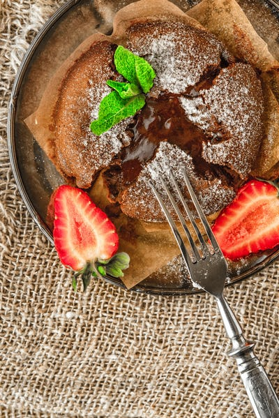 Chocolate fondant  with strawberry and mint on the metal plate