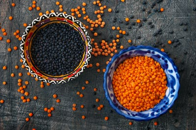 Black and red lentil in the ceramic dishes on the dark backgroun