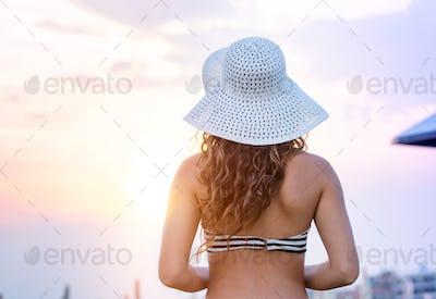 Woman on beach wearing bikini and hat, rear view
