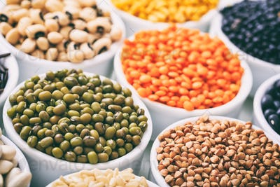 Various raw legumes and rice in bowls