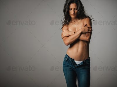 Topless woman looks down as she crosses her arms