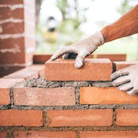 professional construction worker laying bricks and building barbecue in industrial site