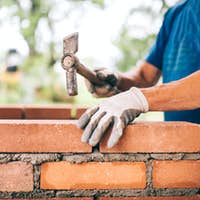 industrial worker building exterior walls, using hammer for laying bricks in cement