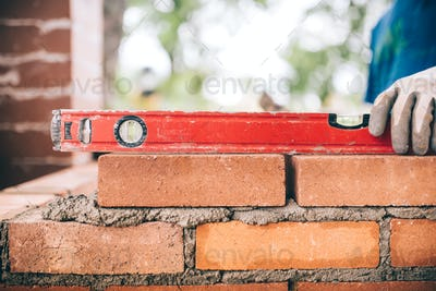 construction worker, bricklayer or mason laying bricks and creating walls. Detail of level tool