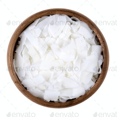 Coconut flakes in a bowl on white background