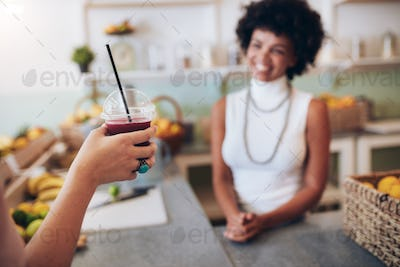 Glass of fresh fruit juice in hand of a customer