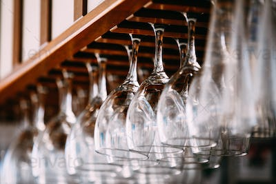 Empty glasses for wine above a bar rack. Hanging wine glasses in