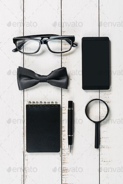 Glasses, black bowtie and pen on white wooden background