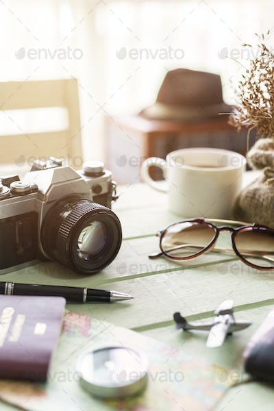 Retro camera with coffee and items on wooden table