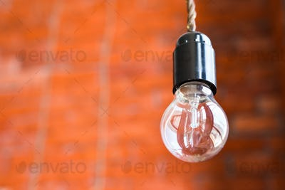 Incandescent lamp on a brick wall background