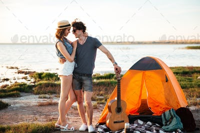 Happy couple in love hugging in front of a tent