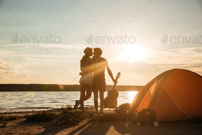 Back view of couple with guitar hugging on the sunset