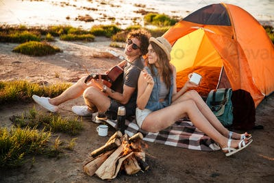 Happy young cheerful couple in love having fun camping