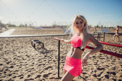 Beautiful fitness athlete woman resting after work out exercising on beach summer evening in sunny