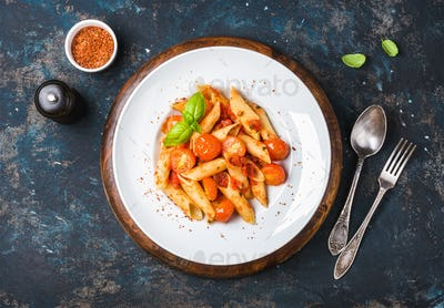 Pasta penne with tomato sauce, fresh basil and roasted tomatoes