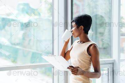 Pensive african american businesswoman with clipboard drinking coffee in office