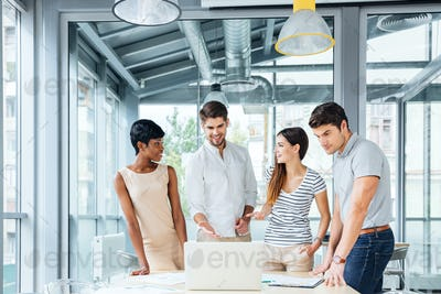Successful business people with laptop standing and talking in office
