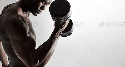 Muscular african male model lifting heavy dumbbells