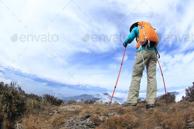 hiker on beautiful rolling clouds mountain peak