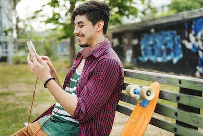 Teenager Boy Texting Skateboard Concept