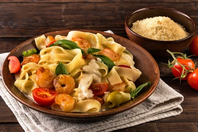 Fettuccine pasta with shrimp and tomatoes on old table