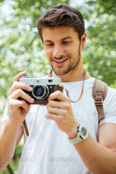 Cheerful man with backpack taking pictures using vintage camera outdoors
