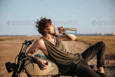 Young brutal man laying on his motorcycle and drinking water