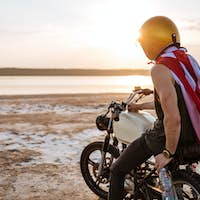 Man in golden in american cape sitting on his motocycle