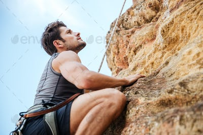 Young man climbing a steep wall in mountain