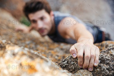 Man reaching for a grip while he rock climbs