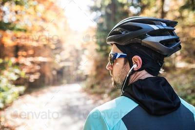 Young sportsman riding his bicycle outside in sunny autumn natur