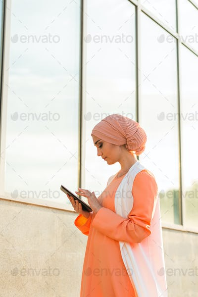 Muslim woman standing , holding document paper