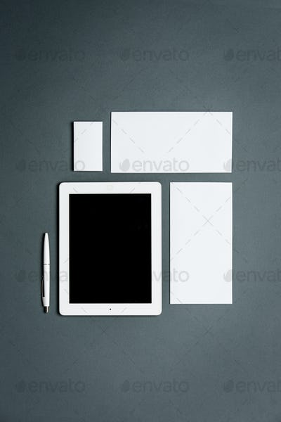 Mock-up business template with cards, papers, tablet. Gray background.