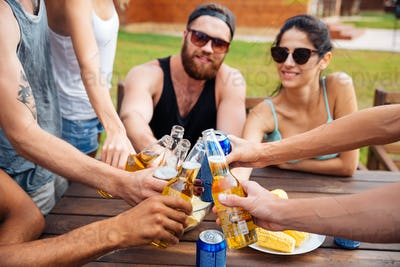Friends celebrating and drinking beer outdoors