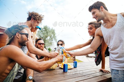 Happy young people with beer celebrating together outdoors