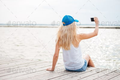Young blonde girl taking selfie with phone on wooden pier