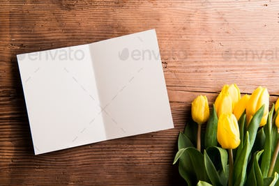 Bouquet of yellow tulips and empty greeting card