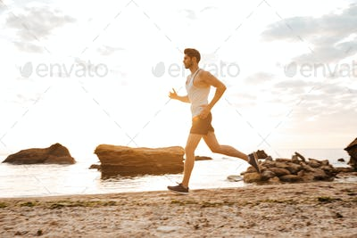 Young sporty man athlete running at the rocky beach